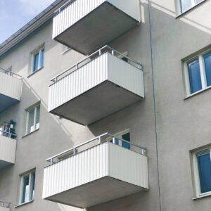 Betongbalkong och vit balkong räcke